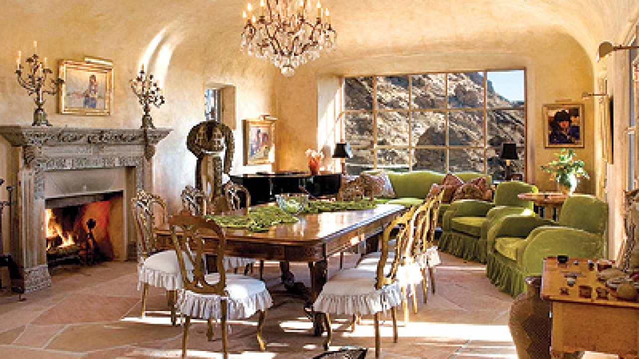 The formal dining room features an arched ceiling and flagstone floor, deep fireplace with Balinese wood mantel, a wet bar, French doors opening onto a deck, and a bay window that brings the natural surroundings into focus. Because of its acoustics, Suzanne Somers enjoys singing in the room, as well as feeding large family gatherings.