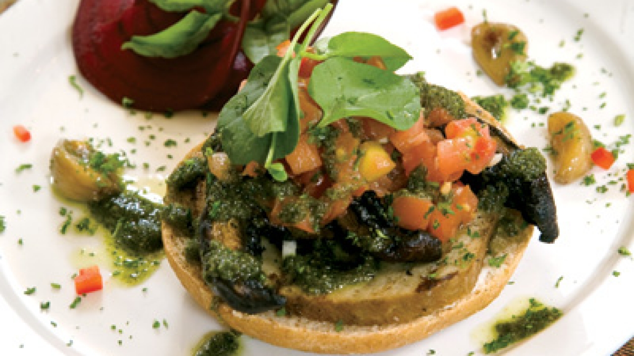 """For the entrée — grilled portobello and Italian """"sausage"""" seitan on crouton with pesto and tomato salsa, served with sweet roasted garlic, beet, and basil, Plummer recommended a tempranillo-based wine like Rioja or Navarra from Spain."""