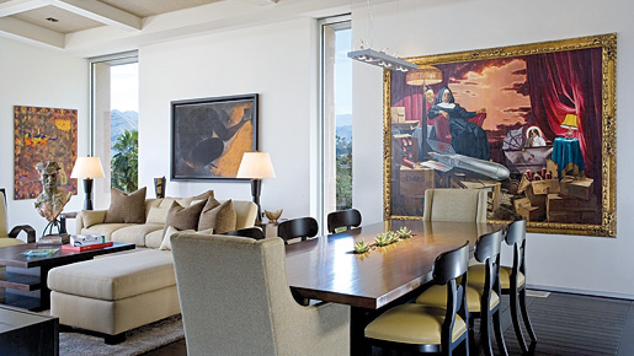 The living and dining rooms become a backdrop for three artists' work. Donald Roller Wilson's irreverant The Clone, The Fuse, and Sister Dinah Might hangs at one end of the dining table; the linear light fixture above the table is Sistemalux. With the flip of a switch, Ricardo Martinez's work over the sofa raises to reveal a flat-screen television. The painting on the front living room wall below the coffered ceiling is by Jesus Urbieta.