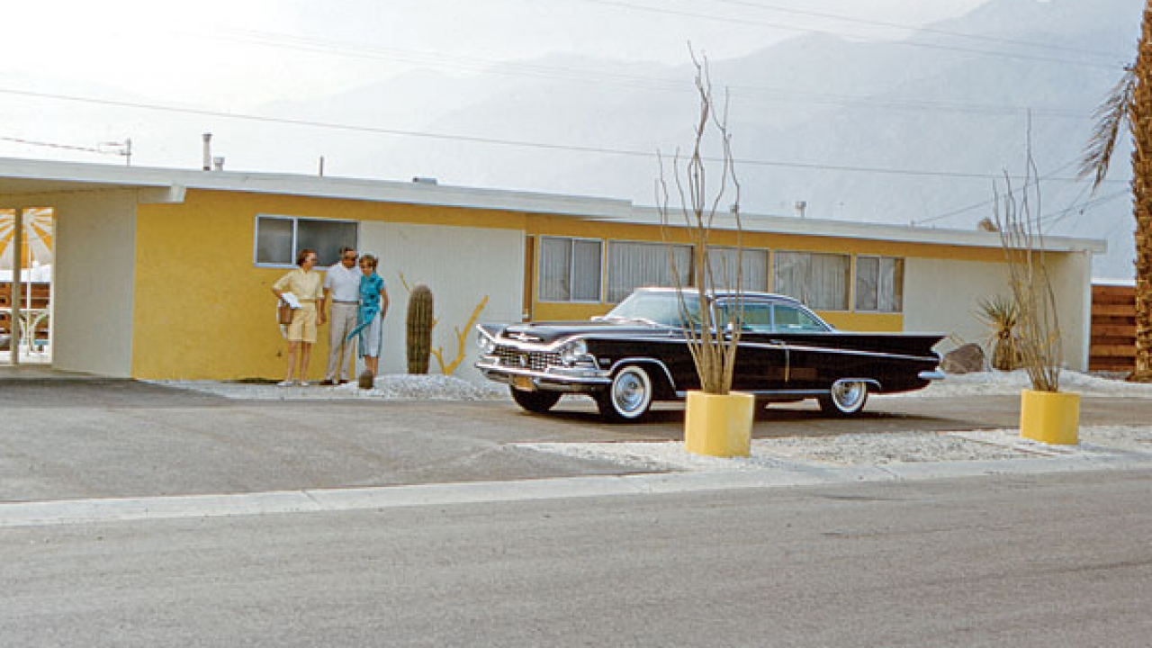 """A lemon meringue-flavored house complete with matching driftwood décor is totally upstaged by the fierce '59 Buick Electra posing in the pass-through driveway."""