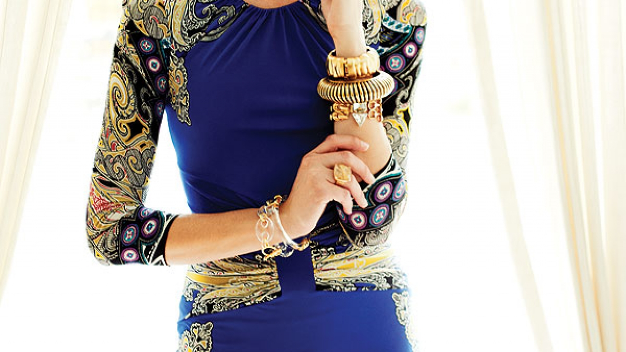 Patterned dress ($1,375) by Etro, at Saks Fifth Avenue. Lucite and gold leaf encrusted earrings ($195), 1970s mod Lucite ring on left arm ($120), matte gold-toned Brutalist cuff ($85), ribbed brass bangle ($75), and crystal and gold-toned link vintage bracelet ($165), at Flow Modern Design. On right arm, acrylic link bracelet and bangle ($165 each) by Alexis Bittar, at Saks Fifth Avenue.