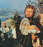Bearded Howard Keel holding an infant child with Lake Cahuilla behind them in The Big Fisherman.